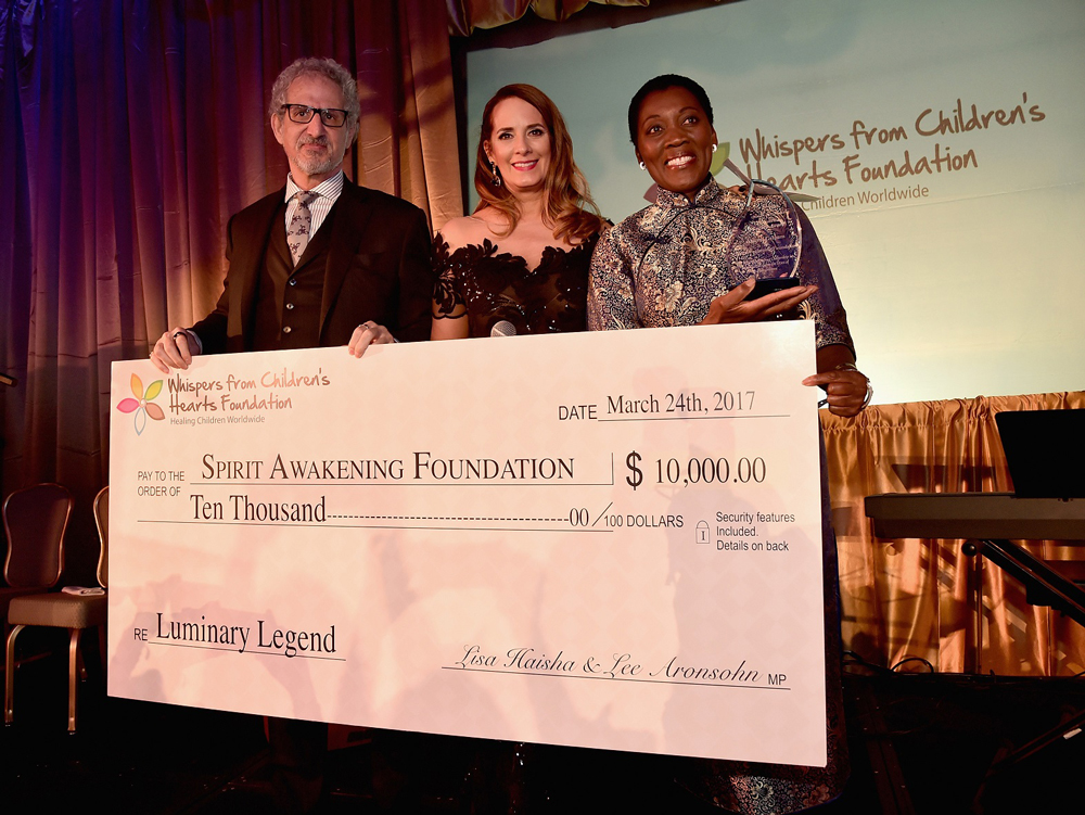 MARCH 24, 2017: Writer/producer Lee Aronsohn and host Lisa Haisha present honoree Akuyoe Graham with a donation for her charity at the 3rd Annual Whispers From Children's Heats Foundation Legacy Charity Gala. (Photo by Alberto E. Rodriguez/Getty Images)